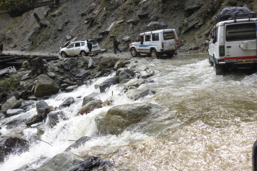 Slow moving traffic, waterfall meets road in Arunachal Pradesh.